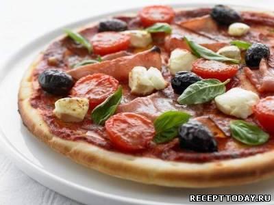 Пицца с ветчиной помидорами и оливками.